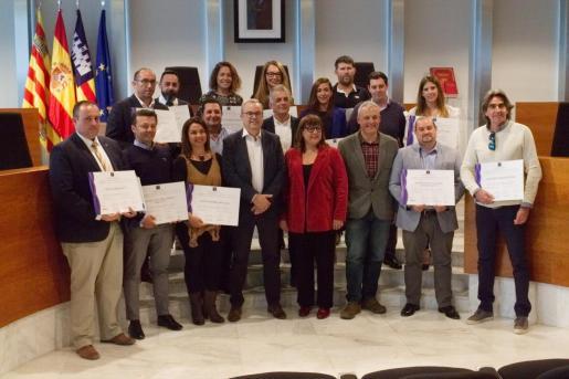 Los representantes de las 17 empresas y establecimientos posan con sus diplomas acompañados junto al presidente, Vicent Torres, y la vicepresidenta del Govern, Bel Busquets.