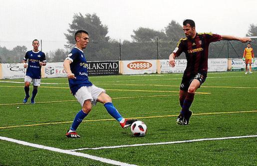 Zurdo pasa el balón ante la presión de un jugador del Poblense.