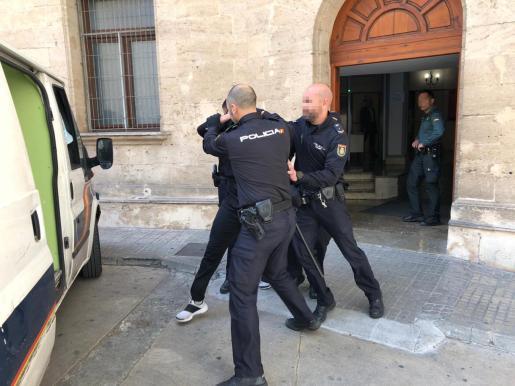 El detenido es custodiado por agentes de la Policía Nacional hasta el furgón que le llevó a la cárcel de Palma.