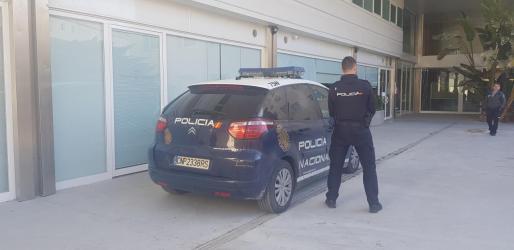 Un agente custodia al detenido que está dentro del vehículo en el patio del Consell.