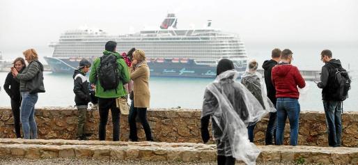 Los turistas recorrieron el casco antiguo de Vila ataviados con chubasqueros y paraguas.