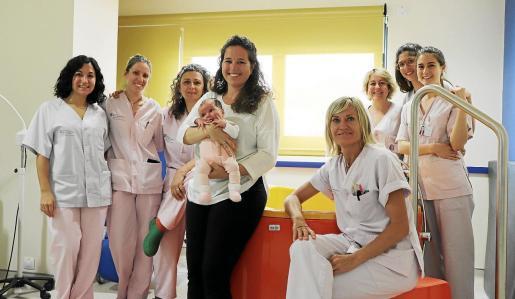 Alheli Scherer, con su hija Uma en brazos rodeada de parte del equipo de Paritorio en la sala donde se encuentra la bañera.
