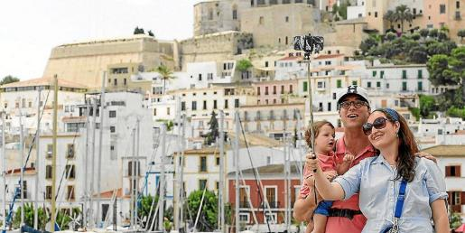 Un matrimonio y su hijo se hacen una foto en el puerto frente a las vistas de Dalt Vila.