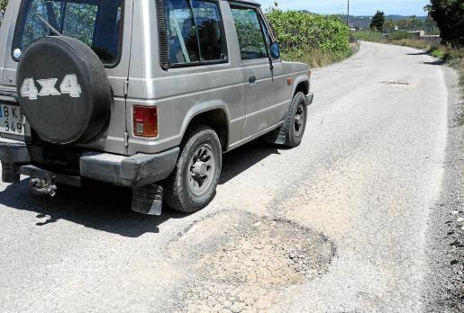 Estado del camino de es Codolar con los baches que denuncian los usuarios y la maleza acumulada.