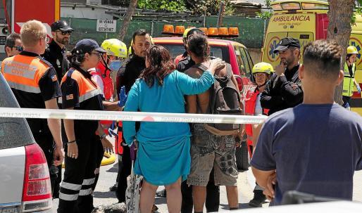 Agentes de la Policía Nacional y sanitarios atienden las indicaciones de unos vecinos de la zona.