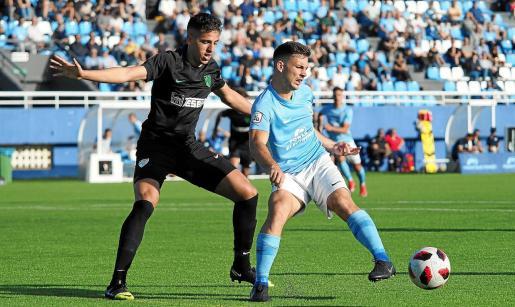 Ángel Rodado, delantero de la UD Ibiza, pasa el balón ante la presión de un jugador del Atlético Malagueño.