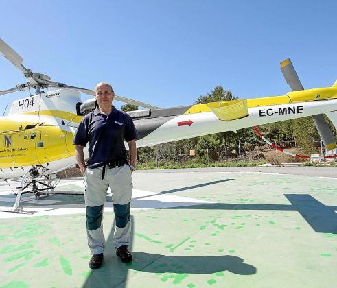 El piloto junto al helicóptero con el que efectuó el rescate de dos personas en el incendio del lunes.