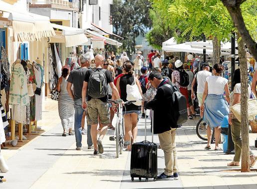 Un turista con su maleta en una calle comercial muy concurrida.