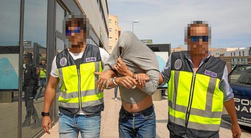 Dos agentes de la UDEV de la Policía Nacional custodian a uno de los detenidos hasta los juzgados de la torre 7 del Cetis.