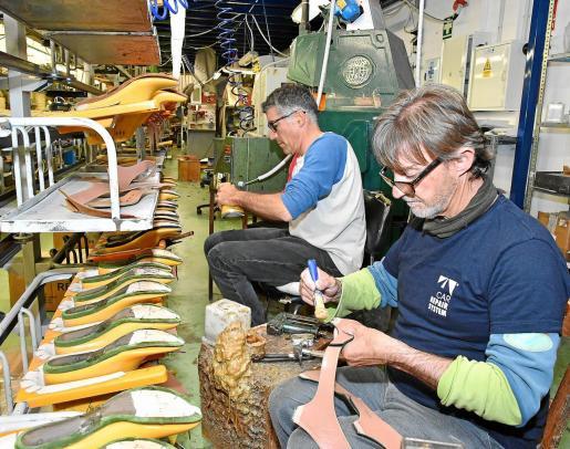 Dos empleados de Homers en pleno proceso de fabricación del calzado, que combina el trabajo artesano con el diseño más moderno. Foto: Sergi Garcia