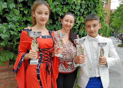Los jóvenes cantantes junto a su profesora Elena Prokhorova y los premios conseguidos en el concurso Alborada Rusa.