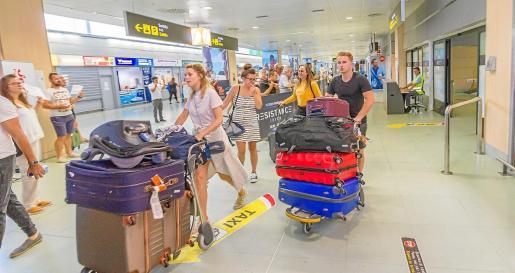 Varios turistas cargados de maletas llegando al aeropuerto de Ibiza.