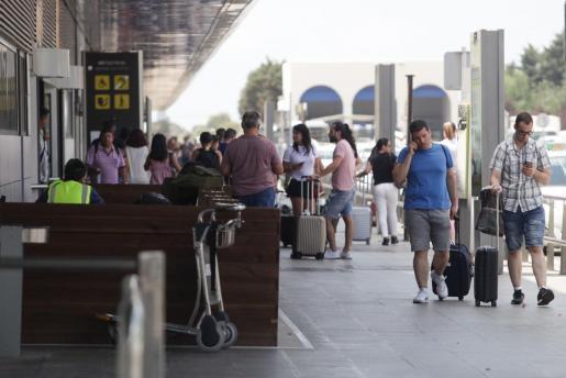 Varios viajeros en el exterior del aeropuerto de Ibiza.