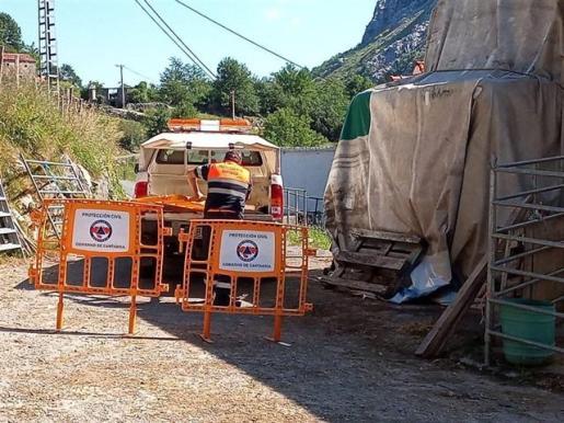 Un agente de Protección Civil valla la zona de acceso a la cueva de Cueto-Coventosa, donde han desaparecido tres espeleólogas de origen catalán.