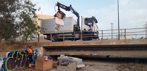 Los operarios desmantelan el asentamiento ilegal.