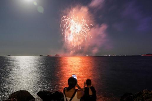 Dos mujeres fotografían los fuegos artificiales que se lanzaron desde s'Illa de ses Rates.