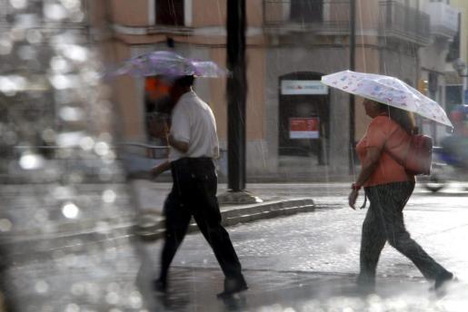 Imagen de archivo de varios peatones con paraguas en un día de lluvia