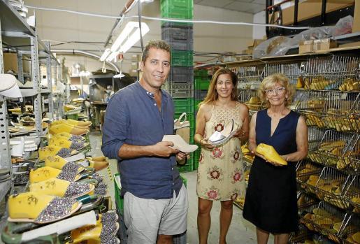 Águeda Pons junto a sus hijos, Joan y Magdalena Villalonga, en la fábrica Llonga's de abarcas de Ciutadella.
