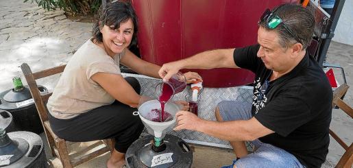 Integrantes de la Comisión de Fiestas pasan el vino de este año a las garrafas.