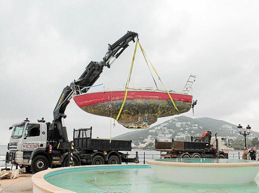 Retirada del barco encallado. Rescate de la embarcación atrapada en las rocas del Paseo Marítimo de Santa Eulària, con un camión grúa.