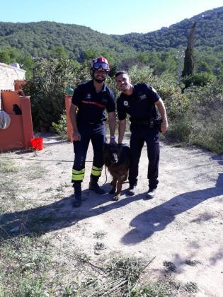 Un efectivo de los bomberos y otro de la Policía Local de Sant Josep posan con el pastor belga.