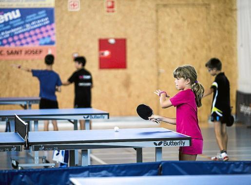 Varios niños practican tenis de mesa.
