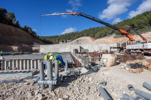 Un grupo de operarios instalan unas tuberías que conformarán la planta de triaje.