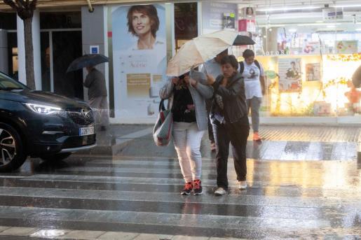Varias personas se protegen con paraguas de la lluvia y el viento en Ibiza.