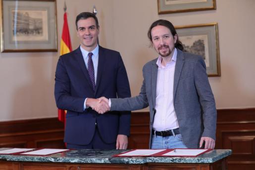 El presidente del Gobierno en funciones, Pedro Sánchez y el líder de Podemos, Pablo Iglesias, se estrechan la mano en el Congreso de los Diputados tras firmar el principio de acuerdo para compartir un gobierno de coalición tras las elecciones generales del pasado domingo, en Madrid (España),el pasado martes.