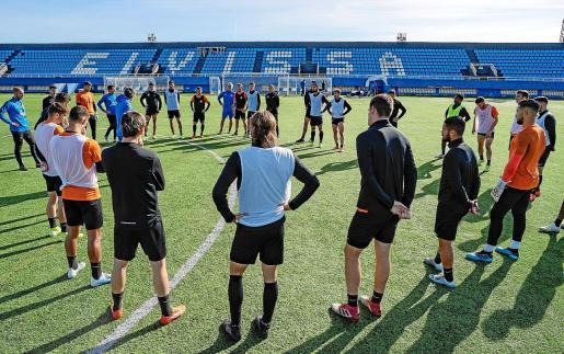 La plantilla de la UD Ibiza permanece atenta a la charla de Pablo Alfaro durante el entrenamiento de ayer.