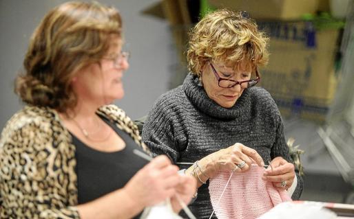 Dos de las integrantes del taller hacen punto y ganchillo mientras conversan.