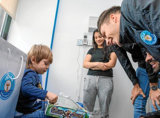Luis Antonio abre un juguete junto a su madre y varios futbolistas de la UD Ibiza, ayer en el hospital de Can Misses.