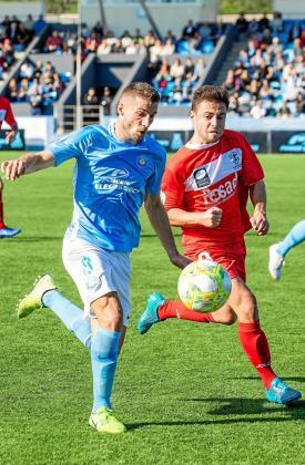 Pep Caballé, perseguido por César Suárez, progresa con el balón controlado.