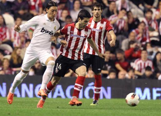 El jugador del Athletic de Bilbao, Susaeta (c), pelea por el balón con el centrocampista alemán del Real Madrid, Mezut Ozil (i).