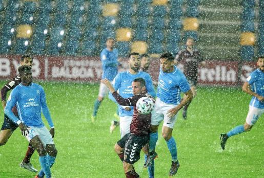 Los jugadores de la UD Ibiza y el Pontevedra disputan el balón bajo la intensa lluvia.