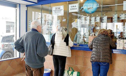 Varias personas comprando lotería para el sorteo de Navidad