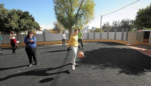 Varios alumnos juegan a fútbol en el patio del colegio.