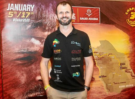 Un sonriente Toni Vingut posa con el cartel del Dakar a su espalda.
