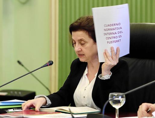 La consellera Fina Santiago muestra la normativa interna del funcionamiento de  Es Pinaret durante su comparecencia en la sala verde del Parlament. Foto: PILAR PELLICER