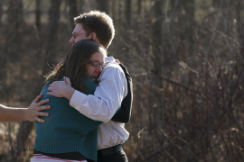 Family members hug outside Sandy Hook Elementary School after a shooting in Newtown, Connecticut