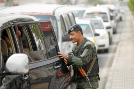 Police trooper checks a car at a checkpoint on road leading to Sanaa International Airport