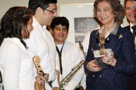 La Reina recibe un violín de la Orquesta de instrumentos reciclados
