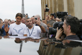 Rafael Nadal of Spain leaves after posing with his trophy for photographers near the Eiffel Tower in Paris
