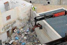 Una grúa retira cinco toneladas de basura de un solar municipal situado en el barrio de sa Penya