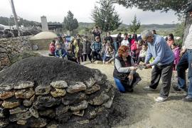 Miquel D'en Trull encendió ayer por la mañana la 'sitja' en compañía de Toni Boned y los niños del colegio público de Santa Agnè