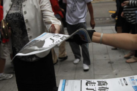 "Workers hand out copies of a special edition of the Sharp Daily bearing the headline ""Steve Jobs Passed Away"" in Hong Kong"