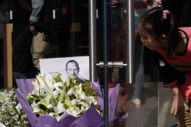 A girl looks at a portrait of Jobs placed with flowers next to the entrance of an Apple retail store in Beijing's Sanlitun