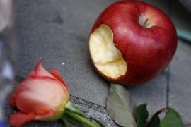 An apple is placed next to a flower offered in memory of Apple co-founder Jobs in Tokyo