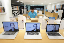 An employee works behind computer monitors displaying the obituary of former Apple CEO Steve Jobs at an Apple Store in Seoul