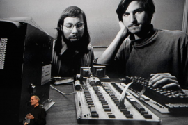File photo of Apple CEO Steve Jobs stands beneath a photograph of him and Apple-co founder Steve Wozniak